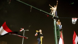 An anti-Morsi protesters flashes the peace sign from a traffic light in Tahrir square, Cairo