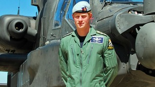 Prince Harry by an Apache attack helicopter