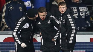 The ball boy who was kicked by Chelsea's Eden Hazard is helped off the pitch.