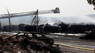 Firefighters work at the scene of a train derailment