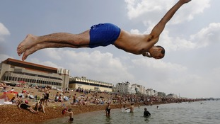 Marek Czyzowski from London dives into the sea at Brighton beach on Sunday. The recent hot weather is due to continue until this Sunday.