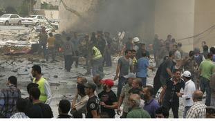 Locals gather round the blast site in the area of Bir el Abed.