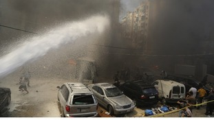 Firefighters and Civil Defence members extinguish the fire in a Hezbollah stronghold.