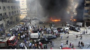 Civil Defence members, security personnel and civilians gather at the explosion site.