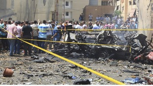 Security personnel and people gather at the site of the explosion in Beirut.
