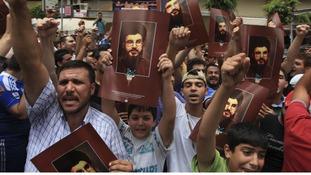 Supporters of Lebanon's Hezbollah leader Sayyed Hassan Nasrallah demonstrate near the blast site.