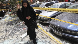 A woman walks over shattered glass past damaged cars in the Hezbollah neighbourhood.