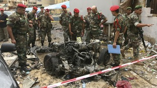 Lebanese military police inspect the remains of a vehicle at the site of today's explosion.