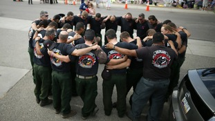 Firefighters pray in front of a memorial dedicated to the 19 firefighters