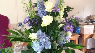 Theflowers are blue and cream and consist of foxglove, freesia and hydrangea.