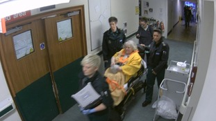 Old lady on bed-trolley in corridor pushed by paramedics