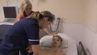 Nurse tends to young boy lying on hospital bed