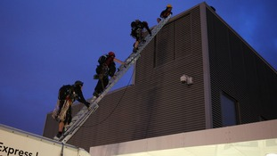 The protesters emerging from the roof of a lorry at the base of The Shard this morning