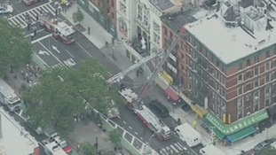 Fire trucks extend their ladders to the building in Lower Manhattan