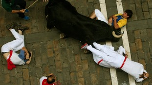A runner holds the horn of an El Pilar fighting bull during the sixth bull run in Pamplona.