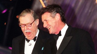 Alan Whicker presenting an award to Michael Palin at the National TV Awards in 1998.