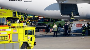 Firefighters climb into a rear cargo compartment of a Japan Airlines Boeing 787 Dreamliner.