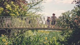 two children on bridge in sun at Spetchley Park and gardens in Worcester