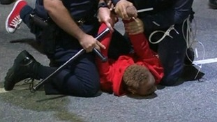 Police officers hold a man on the ground at one of the protests in Los Angeles
