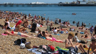 People enjoy the sunshine on Brighton Beach.