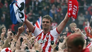 Southampton's Jos Hooiveld is carried off the pitch by fans at the end of the game after the club's promotion to Premier League