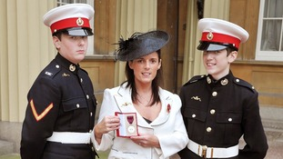 Gillian holding medal with sons