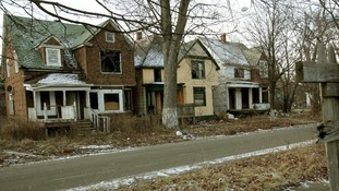 A row of vacant boarded up houses in a once vibrant east side neighbourhood of Detroit, Michigan.