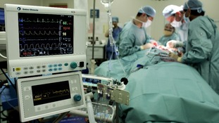 File photo of surgeons carry out an operation to remove a tumour from a patient at an NHS hospital.
