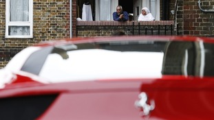 Residents look at a Ferrari from their balcony