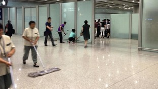 Staff at Beijing Capital International Airport clear up the aftermath of the explosion