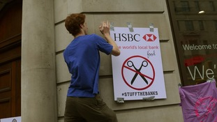 A protester re-brands a HSBC branch in London
