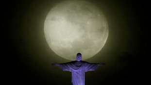 The moon and Christ the Redeemer statue pictured ahead the visit of Pope Francis in Rio de Janeiro.