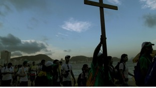 Youths carry a cross on Copacabana beach ahead of World Youth Day in Rio de Janeiro.