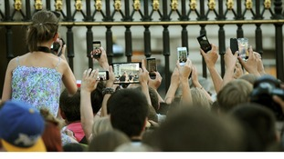 Members of the public try to take photos of an easel in the Forecourt of Buckingham Palace.