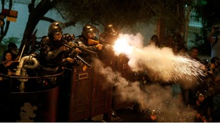 Riot police fire tear gas during a protest during the visit of Pope Francis.