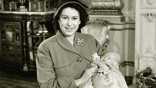 Princess Elizabeth holds her baby son, Prince Charles after his christening in 1948.