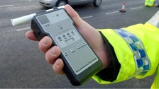 policeman holds breath test kit