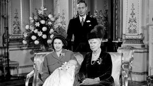 King George VI stands with the now Queen Elizabeth II left) holding her son, Prince Charles.
