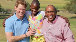 Prince Harry poses with Prince Seeiso of Lesotho and a child that has been helped by their charity.