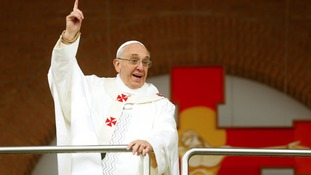 Pope Francis jokes with the crowd while standing on the balcony of the Basilica of the Madonna of Aparecida.