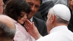 Pope Francis greets a child in the Varginha slum during his visit in Rio de Janeiro.