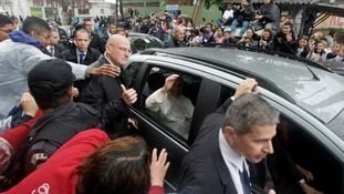 Pope Francis waves to residents as he leaves the Varginha slum in Rio de Janeiro.