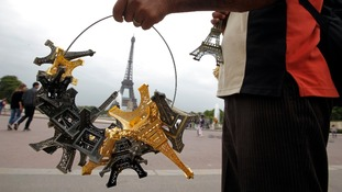 souvenir vendor sells Eiffel tower models for tourists in front of the Eiffel Tower.
