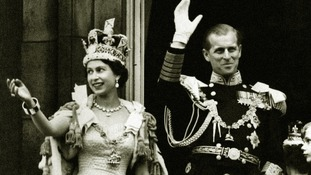 The Queen wearing the Imperial State Crown and the Duke of Edinburgh in uniform on the balcony.