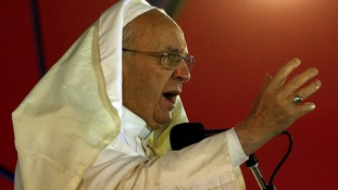 Pope Francis was battered by the wind and soaked with rain but continued to speak to the faithful on the beach.