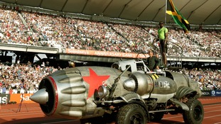 Jamaican sprinter Usain Bolt arrives in the Olympic Stadium on a rocket shaped vehicle.