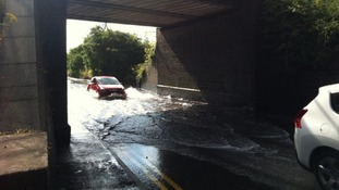 Cars struggle through waters covering the road in Pelsall, Walsall