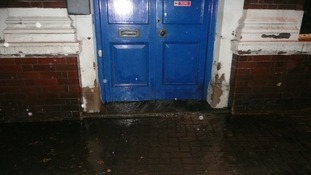 Water pours from under the door of the Harborough Mail offices