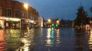 People wade through the waters flooding Market Harborough town centre