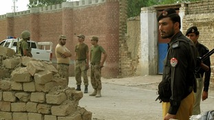 Policemen and ranger soldiers stand outside the prison following the Taliban attack.